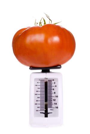 heirloom: Big Brandywine Heirloom Tomato on a Kitchen Scale Stock Photo