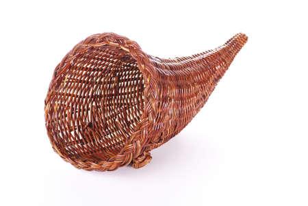 cuerno de la abundancia: Una cornucopia de mimbre aislada en un fondo blanco