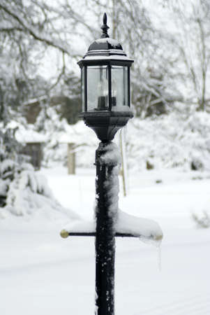 A lamp post covered with snow and ice
