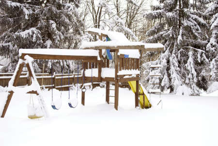 Swing set covered with snow after a blizzard             photo