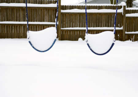 Two swings on a swingset covered with snow in the winter Stock Photo - 8011592