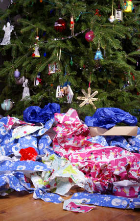 messy: A Mess of Wrinkled Wrapping Paper Scattered Under the Christmas Tree