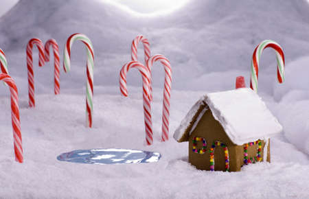 A ginger bread cottage near a candy pond in a snowy candy cane forest Stock Photo