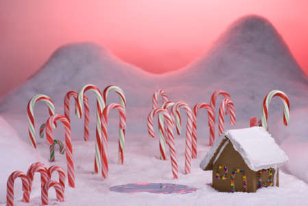 Ginger bread cottage next to a pond in candy cane forest with pink sunset photo