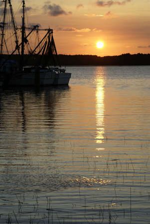 Shrimp boats silhouetted against the sky at sunset