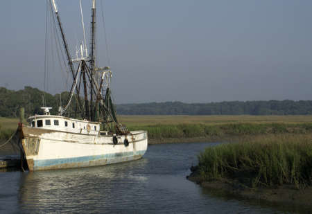 An old shrimp boat docked in a marshy grassland                 photo
