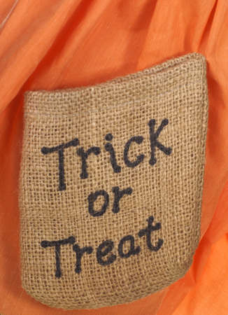 The words trick or treat on a small peice of burlap on orange background                Stock Photo
