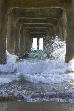 Waves crashing under a concrete pier in California