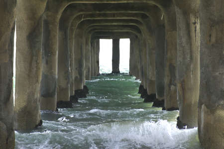 crashing: Waves flowing under a concrete pier in California