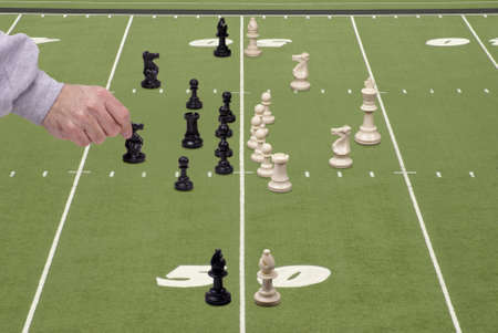 Chess pieces arranged in a football formation with a defensive coach moving the safety. Stock Photo