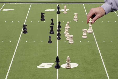 Chess pieces lined up in football formation with the coaches hand moving the quarterback.     Stock Photo