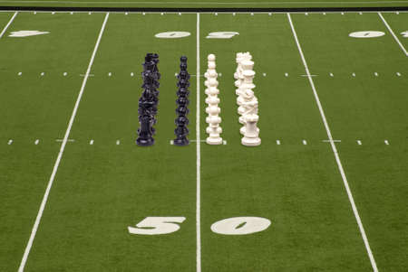 Chess pieces lined up on a football field photo