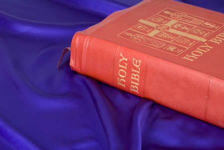 A red and gold leather bible resting on purple silk photo
