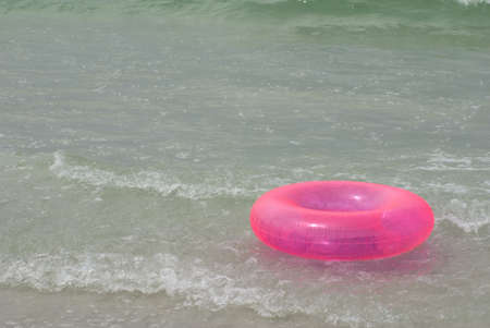 life saver: A pink inflatable life saver floating in the ocean surf