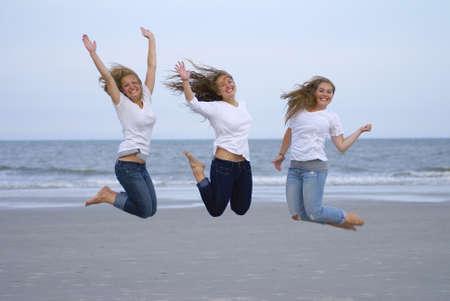 해변에서 기쁨을 위해 점프 세 사춘기 소녀