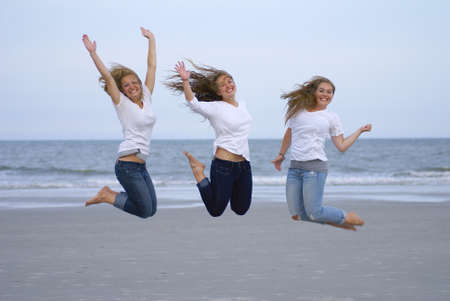 Three teenage girls jumping for joy at the beach         photo