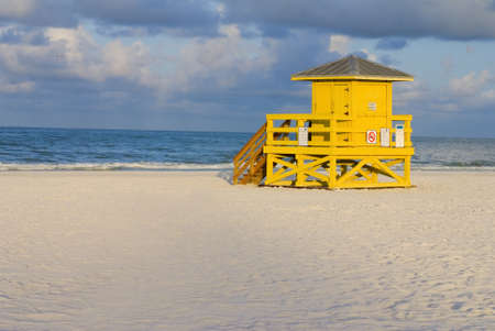 A yellow wooden lifeguard hut on an empty morning beach photo