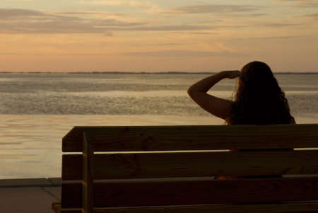 A girl looking at a sunset across the bay