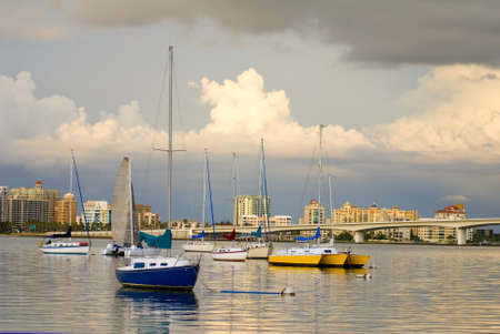 Boats anchored in a harbor under cloudy skies