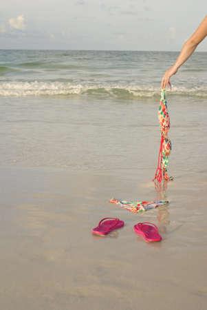 skinny: Ba�arse desnudo concepto de pantalla que muestra el brazo de una mujer dejar a su superior en la playa
