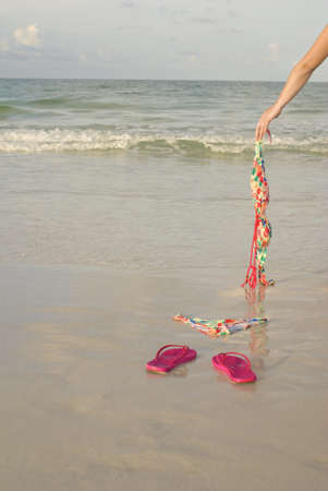 Skinny dipping concept shot showing a woman's arm dropping her top on the beach photo