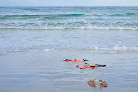 dipping: Skinny dipping concept shot showing a bikini on the beach