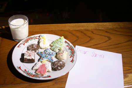 Christmas cookies and milk on a table near a note for Santa at night             Stock Photo