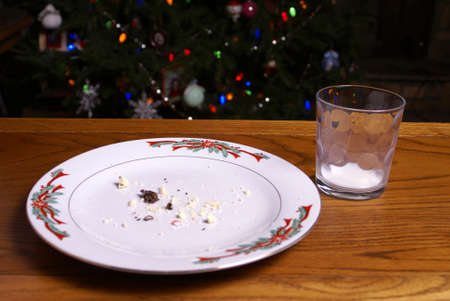 A plate of cookie crumbs and empty glass of milk left by Santa Claus.