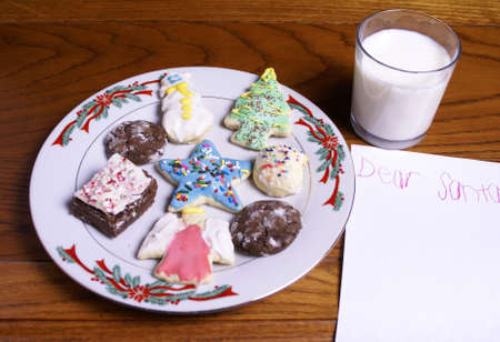 A plate of Christmas cookies and milk by a blank note for Santa Claus. Stock Photo - 16741658