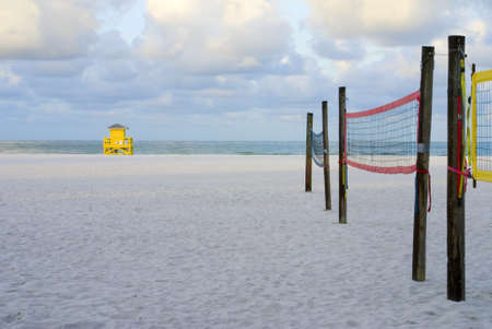 A yellow lifeguard hut and volleyball nets at the beach photo