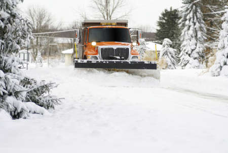 A snow plow coming down the street during a blizzard