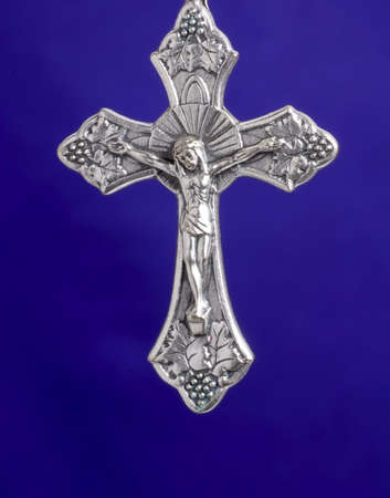 A closeup image of a silver crucifix on purpkle background photo
