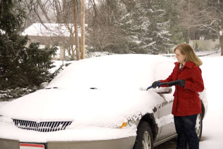 A pretty woman scraping snow off her car during a snowstorm Stock Photo - 17796445