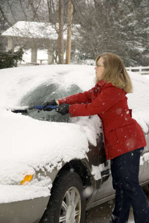A pretty woman scraping snow off her car during a snowstorm Stock Photo - 17796453