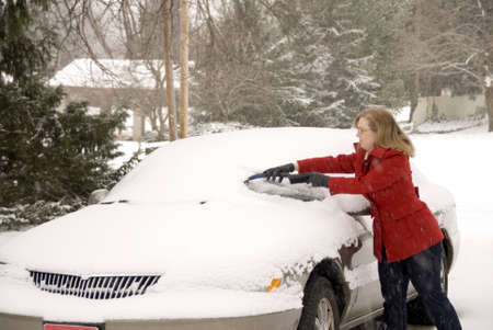 A pretty woman scraping snow off her car during a snowstorm