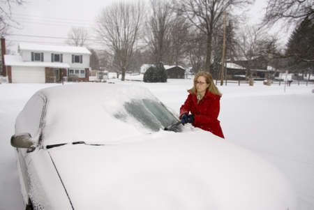 A pretty woman scraping snow off her car during a snowstorm Stock Photo - 17796442