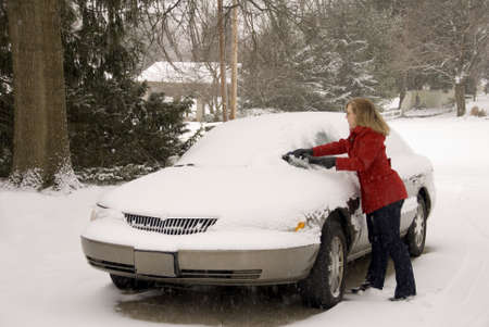 A pretty woman scraping snow off her car during a snowstorm Stock Photo - 17796474