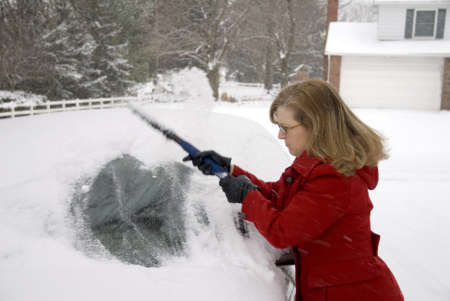A pretty woman scraping snow off her car during a snowstorm photo