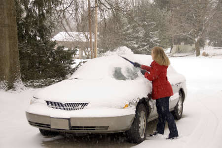 winter road: A pretty woman scraping snow off her car during a snowstorm