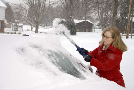 scraping: A pretty woman scraping snow off her car during a snowstorm  Stock Photo
