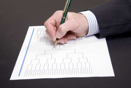 A businessman holdong a pen and doing his basketball tournament bracket Stock Photo