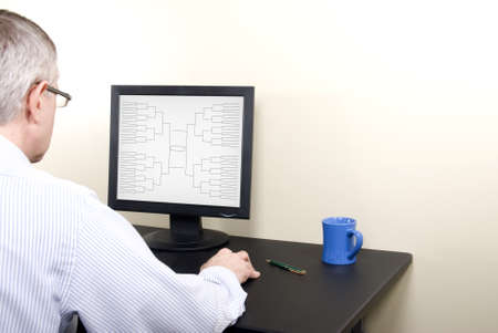 bracket: A man at a computer screen doing his March Madness basketball tournamnet bracket  Stock Photo