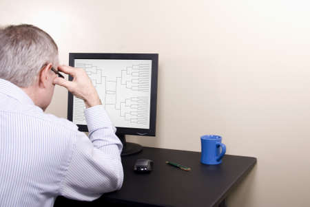 A man at a computer screen doing his March Madness basketball tournamnet bracket  Stock Photo