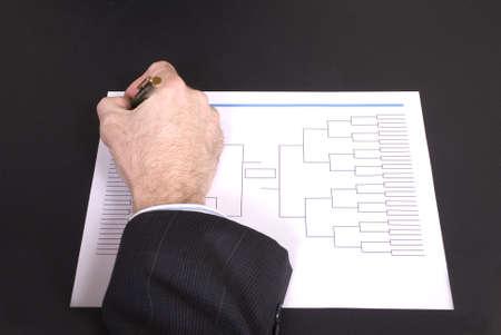 bracket: Closeup of a businessmans hand holding a pen completing tournament bracket Stock Photo