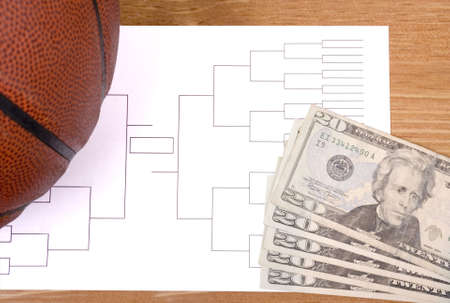 A basketball, tournament bracket and twenty dollar bills
