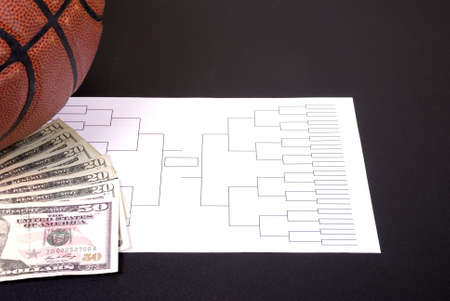 A March Madness tournament bracket with a basketball and fanned money
