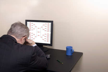 A businessman with his head down lamewnting his busted March Madness bracket. photo