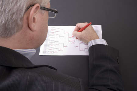 A businessman crossing out teams on his busted March Madness bracket photo