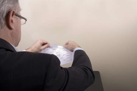 bracket: A businessman tearing his losing March Madness bracket in frustration