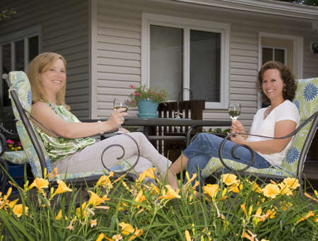 Two pretty women enjoying wine on a patio framed by yellow lilies
